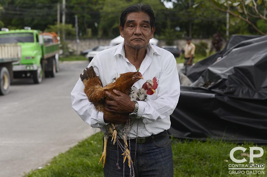 René  Sánchez carga  dos de sus animales de crianza mientras espera que carguen el camión que llevará sus cosas a casa de su hijo, en San Juan Opico. René vivió en la Comunidad El Espino desde 1974.
