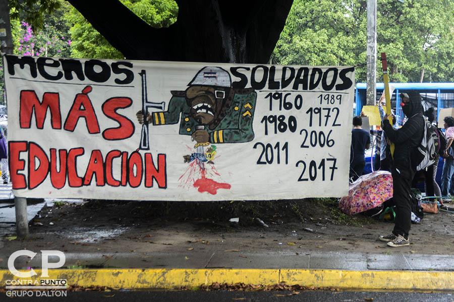 Estudiantes universitarios, artistas urbanos y miembros de la sociedad civil protestaron a las afueras de la Universidad de El Salvador contra el uso de militares para realizar labores de seguridad en San Salvador.
