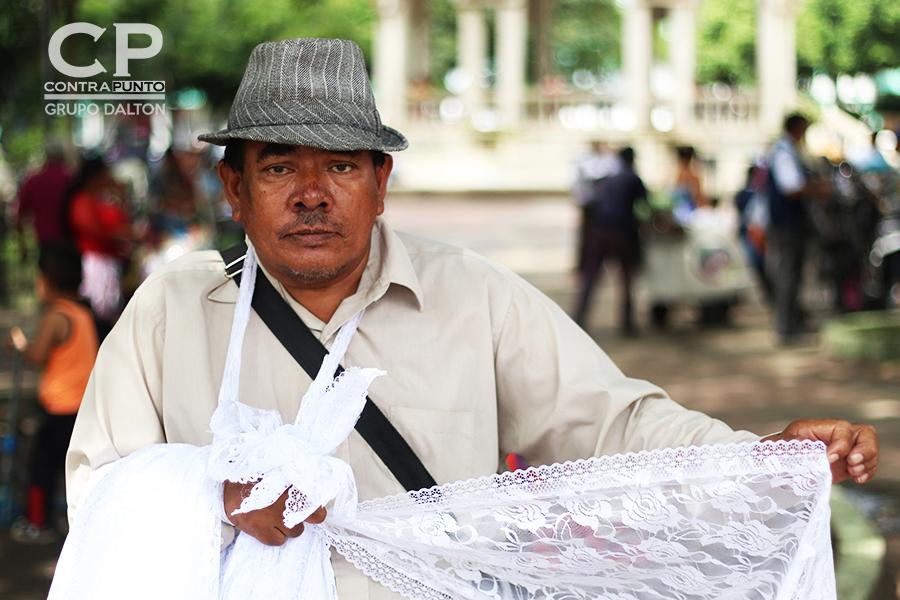 Don Miguel Ángel comercializa velos en las afueras del mercado de Santa Tecla, está ahí todos los días desde las 5 de la mañana.