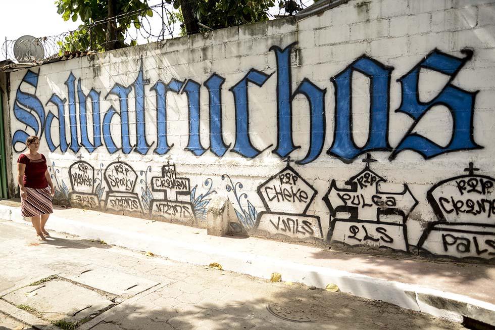 Una mujer camina frente a un grafiti de la Mara Salvatrucha en la comunidad 22 de abril, en Soyapango, lugar donde el gobierno lanzó de manera oficial el 21 de junio el plan