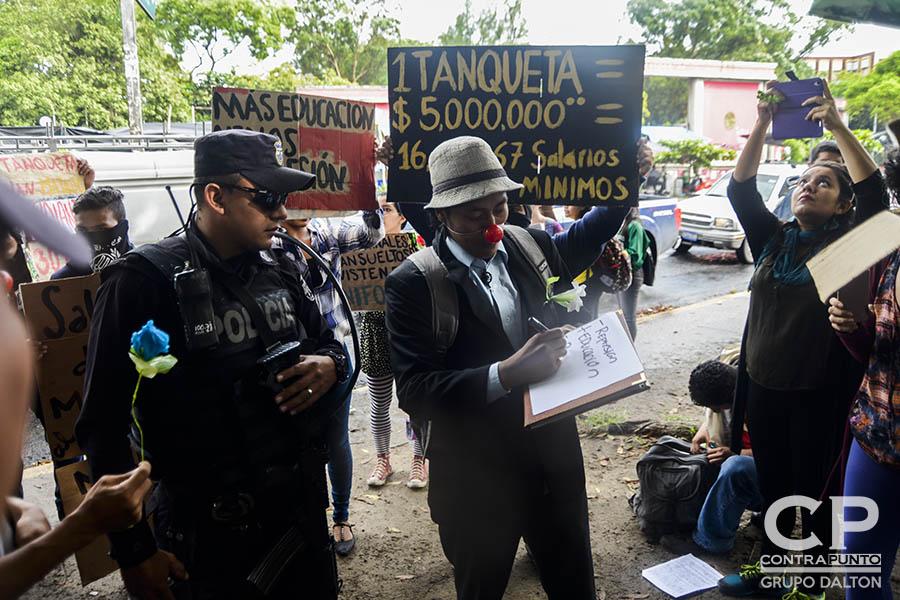Estudiantes universitarios, artistas urbanos y miembros de la sociedad civil protestaron a las afueras de la Universidad de El Salvador contra el uso de militares para realizar labores de seguridad en San Salvador, un nuevo plan del Gobierno para reducir la criminalidad en la capital.