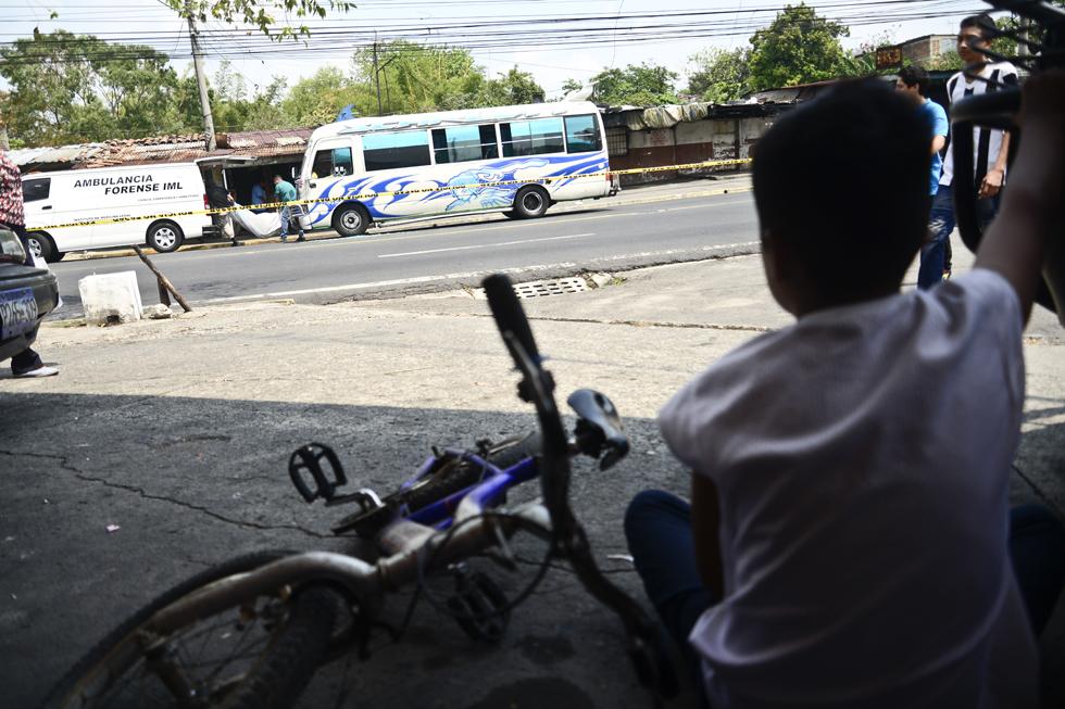 Un niño ve el traslado del cuerpo de un motorista de la ruta 6A que fue asesinado en las afueras del municipio de Mejicanos. Foto: Jessica Orellana
