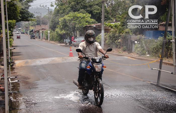 Motociclista pasando por el arco de desinfección